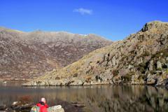 Walker at Crib Goch reflected in Llyn Llydaw