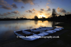 Sunset over the Colourful wooden rowing boats for hire on the Mere at Thorpeness village, Suffolk County, England