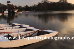 Spring, April, May, June,  Sunset over the Colourful wooden rowing boats for hire on the Mere at Thorpeness village, Suffolk County, England